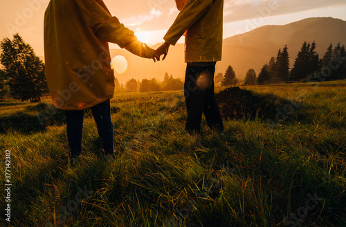 Fotografie, Obraz Couple of hikers holding hands standing in the grass in the rain on a background of sunset in the mountains