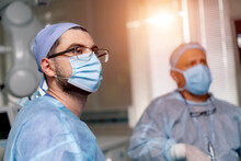 Two Surgeons In Operating Theater. Doctors In Scrubs Providing Operation With Modern Equipment. Selective Focus.