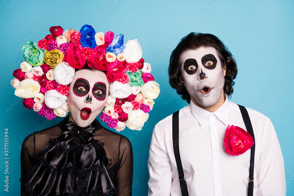 Fototapeta Photo of zombie ghost couple man lady shocked open mouth speechless find out themselves underworld wear black dress death costume roses headband suspenders isolated blue color background