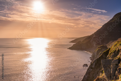Fototapeta Dramatic sunrise with sun star on a Cliff Walk between Bray and Greystones with