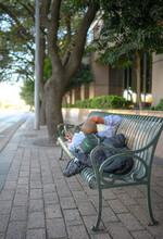 Homeless Sitting On Bench In Park
