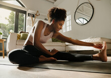 Beautiful Smiling Woman Stretching After Long Yoga Flow Sitting On Yoga Mat In Modern Lounge