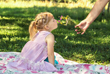 Woman's Hand Holds Out A Bouquet Of Wild Flowers To A Little Girl In The Park