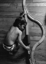 Black And White Photo Of Boy Playing With Train Track