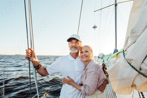 Fotografie, Obraz Loving senior couple enjoying vacation and looking to the distance