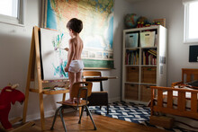 Boy Stands On Chair To Paint