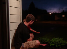 Father And Son Sit On Porch At...