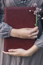 Young Woman Holding A Old Book And Flowers