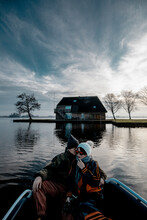 Beautiful Mature Couple Having Fun Sitting On A Original Boat On The Lake In A Winter Day
