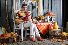 Mom And Daughter Sit On A Chair In Halloween Decorations