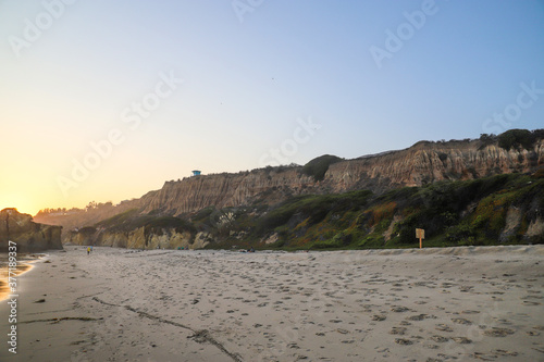 Slika na platnu a lush green hillside at the beach at sunset at El Matador beach in Malibu Calif