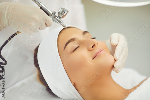 Obraz na płótnie Smiling womans face getting oxygen therapy or jet peeling from cosmetologist