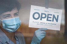 Close Up Of Woman Hand Holding Sign Wear Mask Before Open Wearing Mask For For Prevent Corona Virus Infection - Reopening After Restaurant Lock Down - Focus On Sign And Hand