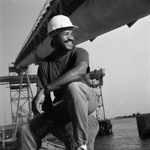 Canvas Print African American male welder next to water
