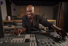 Portrait Of Smiling Man Working At Audio Control Panel