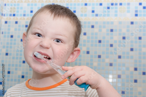 Photo little boy brushes teeth in the bathroom