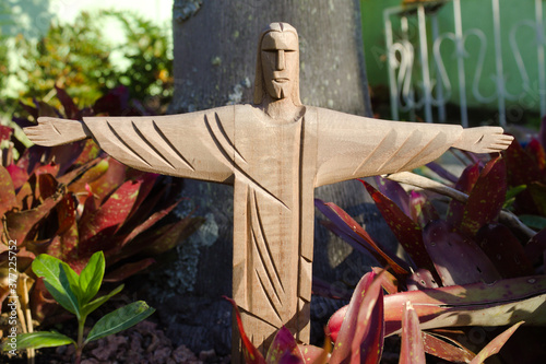 Fotografija Cristo em um jardim com os braços aberto