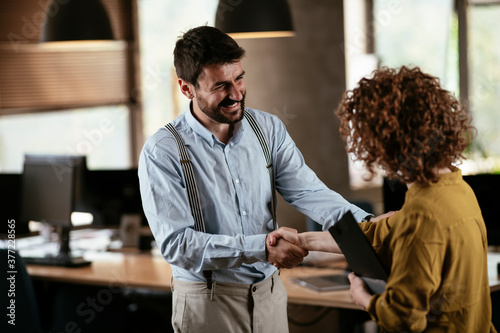Obraz Businesswoman and businessman discussing work in office. Two friends handshake in office.. - fototapety do salonu