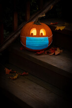 Illuminated Lighted Jack-o-Lantern Dressed Up For Halloween With COVID Pandemic Face Mask