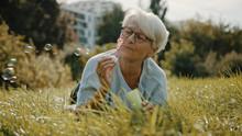 Retired Senior Woman Enjoying Freedom. Childish Grandma Blowing Soap Bubbles In The Park. High Quality Photo