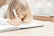 beautiful little blonde girl lies on the floor and writes something in a notebook. low contrast image with copy space. selective focus on hand