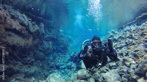 diver in drysuit swimming in icelandic glacial water Wallpaper Mural