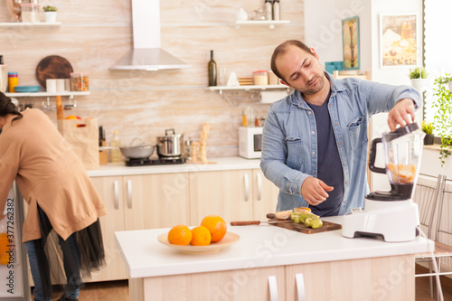 Man mixing fruits in blender while wife is looking inside refrigerator Fototapet