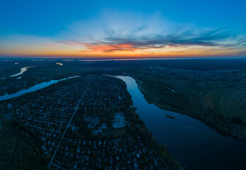 Panoramic aerial view of the nature landscape with green meadows and a river at sunset.