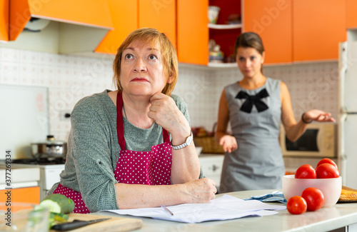 Valokuva Quarrel of an elderly mother and adult daughter in the kitchen