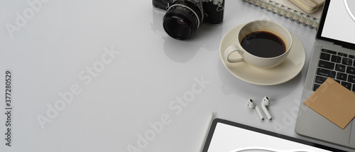 Photo Worktable with copy space, laptop, mock up tablet, coffee cup and accessories