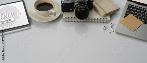 Photo Worktable with copy space, laptop, mock up tablet, notebooks, camera, coffee cup
