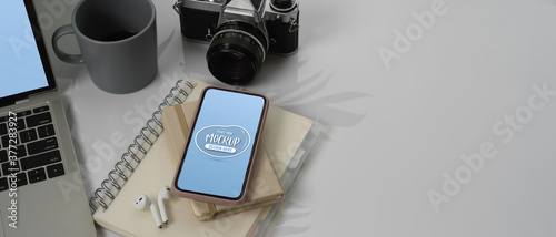 Mock up smartphone on worktable with mock up laptop, camera and copy space Canvas Print