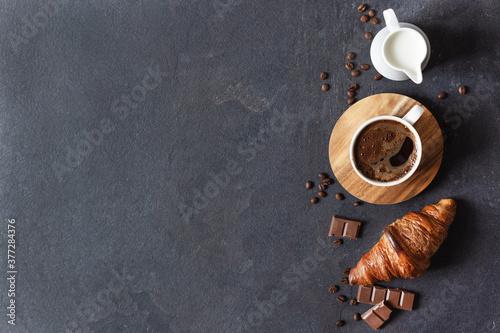 Fototapeta Coffee cup, milk and croissant on black background top view. obraz na płótnie