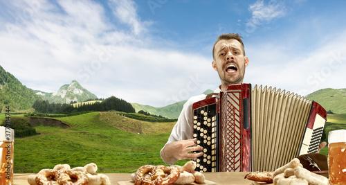 Happy smiling man with beer dressed in traditional Austrian or Bavarian costume holding mug of beer, singing Fotobehang
