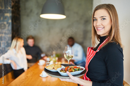 Fototapeta Freundliche Kellnerin serviert Vorspeisen