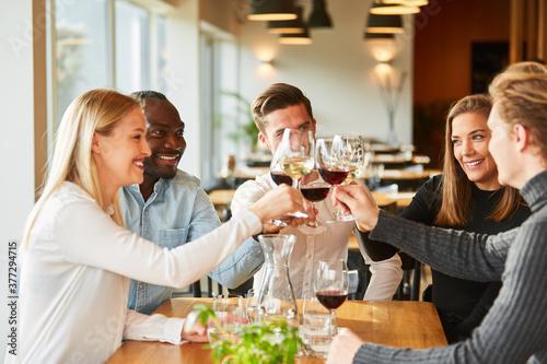 Fényképezés Freunde stoßen an mit Wein und feiern