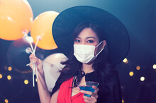 Portrait Of Beautiful Young Woman In Witch Halloween Costumes Wearing Protection Face Mask Against Coronavirus Drinking Cocktails At Party Over Dark Magic Background - Halloween Party Concept