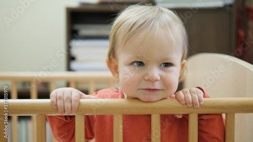 Obraz na plátně Portrait of sweet baby stand in crib smile, look and babble, innocent expressive