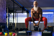 Senior Fitness Man Doing Kettle Bell Exercises Inside Gym - Fit Mature Male Training In Wellness Club Center - Body Building And Sport Healthy Lifestyle Concept