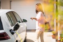 Close Up Of A Electric Car Charger With Female Silhouette In The Background, Locking A Car