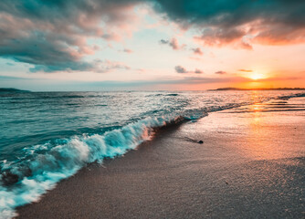 Ocean sunset, waves washing in over the sand. Strong sunset colors and clouds over the horizon