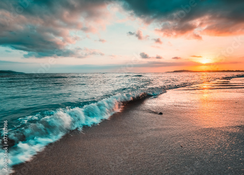 Obraz Ocean sunset, waves washing in over the sand. Strong sunset colors and clouds over the horizon - fototapety do salonu