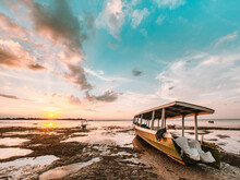 Indonesian Fishing Boat On The Beach At Low Tide. Strong Sunset Colors And Reflections And Reflections In The Water