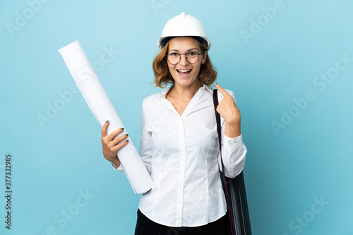 Fototapeta Young architect Georgian woman with helmet and holding blueprints over isolated background giving a thumbs up gesture obraz