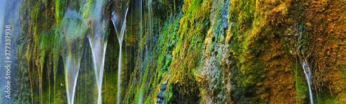 Waterfall close-up, an orange cliff with green moss. Etretat, Normandy, France. Colorful abstract nature pattern, texture, panoramic background, wallpaper, graphic resource. Environment, pure nature