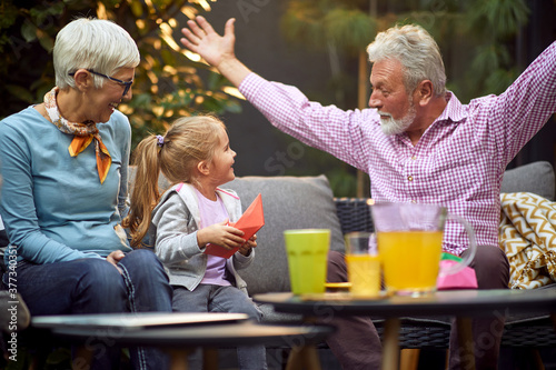 grandfather amusing his granddaughter, telling story with his arms spread Canvas Print