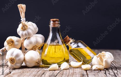 Fototapeta Glass bottle of garlic oil and Ripe and fresh garlic plant on wooden or rustic table, alternative medicine, organic cleaner. obraz