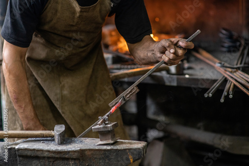Fotografia Blacksmith bends iron rod on the anvil with tool