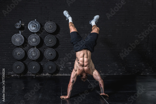 Fototapeta Young strong fit muscular man doing hand stand and walk in the gym as hardcore cross workout training obraz