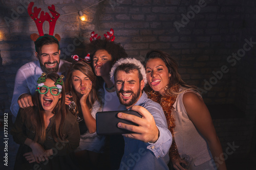 Friends making crazy faces while taking selfies at New Year party Canvas-taulu